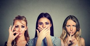 Держите секретное для того чтобы быть тихой концепцией 3 скрытных молодой женщины держа рот закрытый стоковые изображения rf