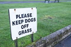 Держите собак со знака травы стоковое изображение rf