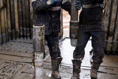 Деррик Ассистентский бурильщик вытягивает бурильную трубу с крюком в защитных перчатках Безопасность в сверлить нефтяных скважин  стоковая фотография