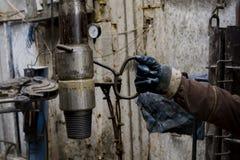 Деррик Ассистентский бурильщик вытягивает бурильную трубу с крюком в защитных перчатках Безопасность в сверлить нефтяных скважин  стоковое фото rf