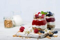 десерты с пюрем granola, ягоды и плодоовощ в опарниках Стоковые Изображения
