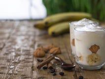 Десерт банана с шоколадом, сливк, печеньями и циннамоном на белой таблице Стоковое Изображение RF