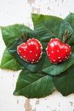 Десерт в форме сердца лежит на зеленых листьях на старой деревянной предпосылке, конце-вверх Стоковое Фото