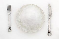 Десерт зимы Белая плита вполне снега на snowbank с близко лежа серебряными вилкой и ножом Стоковое Изображение RF