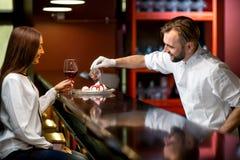 Десерт сервировки кашевара шеф-повара к клиенту Стоковые Фотографии RF