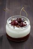 Десерт с вареньем сливк и вишни на темной деревянной предпосылке Стоковая Фотография RF