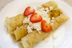 Десерт сделанный от блинчиков заполненных с творогом и клубниками На таблице в белой плите Стоковые Фото