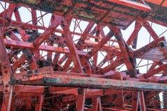 Детализируйте взгляд вращая красного колеса затвора распаровщика колеса затвора, с водой брызгает и slight запланированную нерезк Стоковые Изображения