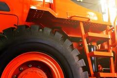 Детали современного красного конца трактора вверх, нижний взгляд, черные автошины стоковое фото rf