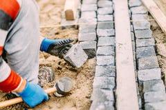 Детали строительств при промышленный работник устанавливая блоки булыжника гранита на пути или переулке Стоковые Фото
