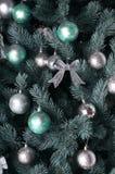 Детальное фото рождественской елки украшенной с подарками, яркими покрашенными сферически игрушками, лентами и концом-вверх гирля Стоковые Изображения RF