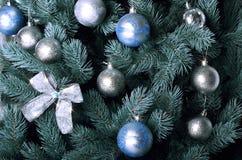 Детальное фото рождественской елки украшенной с подарками, яркими покрашенными сферически игрушками, лентами и концом-вверх гирля Стоковое Изображение
