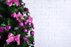 Детальное фото рождественской елки украшенной с подарками, яркими покрашенными сферически игрушками, лентами и концом-вверх гирля Стоковые Фото