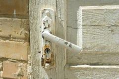 Деталь белой винтажной деревянной двери с покрашенной треснутой ручкой двери Стоковая Фотография