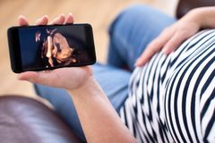Деталь беременной женщины смотря изображение 3D младенца на мобильном телефоне стоковые фотографии rf