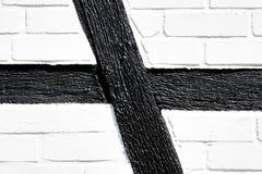 Деталь бортовой стены полу-timbered дома с черными деревянными балками и побеленными стенами кирпичей грязи Стоковая Фотография