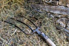 Деталь вилы отдыхая на куче сена в деревенском камне b Стоковые Фото