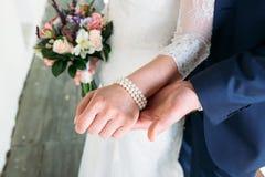 Деталь держать букета и рук ` s невесты Стоковое Фото
