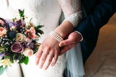 Деталь держать букета и рук ` s невесты Стоковая Фотография