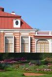 Деталь дома, окна, кирпичи, окно круга барочное, сдобренные окна, исторический стиль, архитектура, сад, парк, цветки, стоковое изображение rf