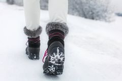 Деталь женщины поднимая ее черный и серый ботинок снега стоковые изображения rf