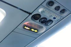 Деталь интерьера кабины самолета Сигнал для некурящих и ремня безопасности стоковая фотография