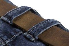 Деталь кожаного пояса на голубые джинсы изолированные на белой предпосылке Стоковые Изображения RF
