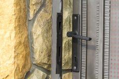Деталь конца-вверх загородки известняка около жилого дома и закрытой железной двери строба с ручкой замка и металла Каменный maso Стоковая Фотография RF