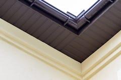Деталь конца-вверх угла дома коттеджа с коричневый вставать на сторону планок металла и крыши со стальной системой дождя сточной  стоковое фото