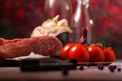 Деталь красных томатов рядом с tenderloin свинины на деревянной доске Стоковое фото RF