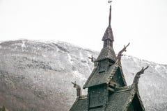 Деталь 1000 - летнее сложного ударяет церковь в Норвегии с покрытой снег горой в предпосылке стоковое изображение