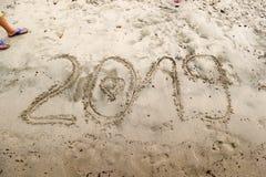 Деталь молодых ног ` s мальчика стоя около 2019 написанного на песке моря с вычерченным сердцем в 0 Стоковые Фото