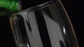 Деталь свежего пива лить от бутылки в стекло на черной предпосылке сток-видео
