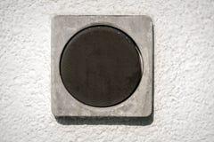 Деталь темного квадратного переключателя на белой стене Стоковые Изображения