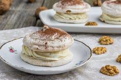Детализируйте на меренге грецких орехов с какао на белой плите Стоковая Фотография
