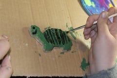 Детали картины ребенка на черепахе Стоковые Изображения
