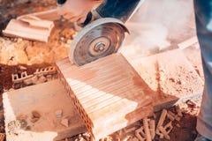 Детали работника используя угловую машину для резать кирпичи на строительной площадке Стоковое Фото