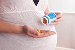 Деталь беременной женщины принимая витамины Стоковые Изображения