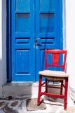 Деталь красочной голубой двери и красного деревянного стула Стоковое фото RF