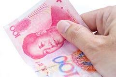 Деталь мужской руки держа 100 китайских банкнот RMB на whi Стоковое Фото
