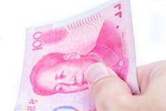 Деталь мужской руки держа 100 китайских банкнот RMD на whi Стоковые Изображения