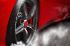 Деталь на закручивать, перемещаясь колесо красного супер спорта Стоковые Фотографии RF
