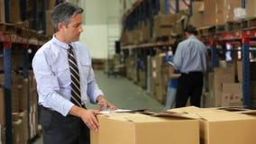 Деталь проверяя коробки бизнесмена с доской сзажимом для бумаги акции видеоматериалы