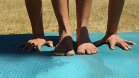 Деталь рук и ног женщины делая йогу на циновке йоги в парке Стоковые Фотографии RF
