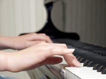 Деталь рук подростка играя рояль Стоковые Изображения