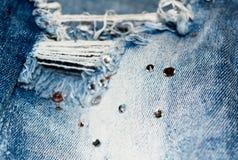 Деталь сорванных джинсов текстура джинсыов ткани детали джинсовой ткани хлопка Прямоугольная предпосылка Стоковое Изображение