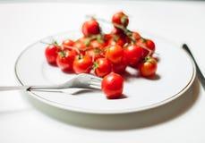 Деталь томата с вилкой на плите стоковое фото