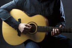 Деталь человека играя акустическую гитару Стоковое Изображение