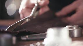 Деталь, человек с ножницами режет кожу видеоматериал