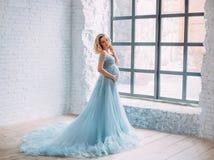 Детеныши, беременная женщина представляя в роскошном, сочном, голубом платье с длинным fairy поездом Предпосылка свет стоковое фото